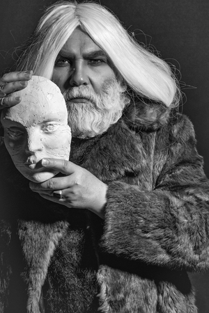 old druid bearded man with long beard on serious face and hair in fur coat holding white sculpture head in hands with ring on dark background