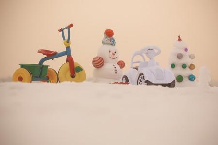 눈사람과 눈 크리스마스 트리 장미 빛 하늘에. 겨울 휴가 축 하 개념. 크리스마스와 새 해입니다. 눈 덮인 배경에 세 발 자전거 및 장난감 자동차입니다 스톡 콘텐츠