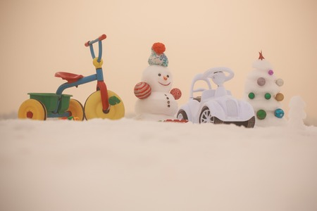 Snowman and snow xmas tree on rosy sky. Winter holidays celebration concept. Christmas and new year. Tricycle and toy car on snowy background. Festive surprise and presents.