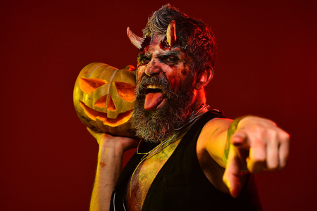 Halloween satan show tongue with bloody horns, beard, blood, wounds. Man devil hold pumpkin on red background. Trick or treat. Darkness and light concept. Demon point finger with jack o lantern.