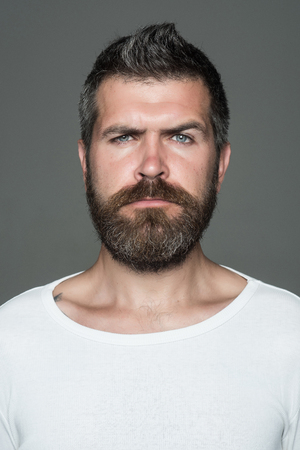 Hipster with serious face. Man with long beard and mustache. Guy or bearded man on grey background. Feeling and emotions. Barber fashion and beauty. 版權商用圖片