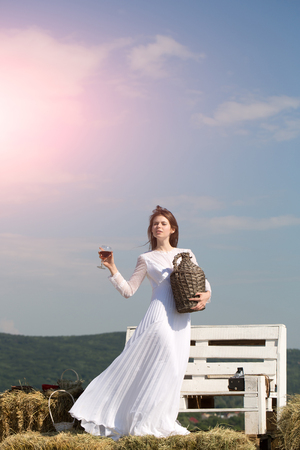 Girl in white dress posing on blue sky. Summer vacation, holidays and celebration. Model with alcohol drink on sunny day. Winery tour concept. Woman with glass of red wine and wicker bottle. Stock Photo
