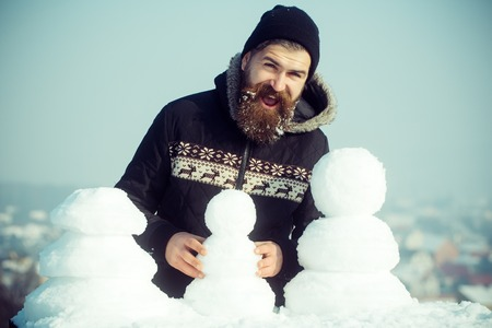 Christmas man with long beard. Santa claus hipster in coat and snowman. Snowman family made of white snow New year guy on blue sky with snow figure. Winter holiday vacation and xmas party celebration. Stock Photo