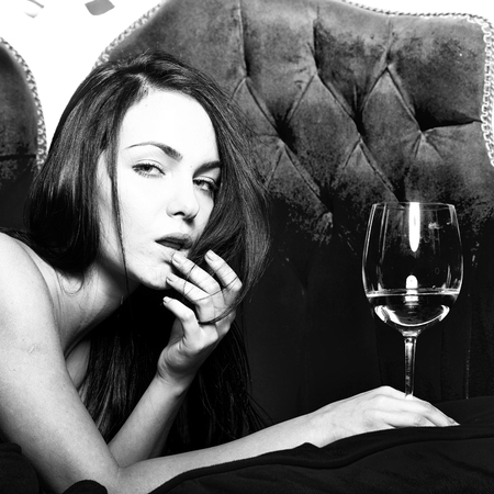 One pretty sexual naked brunette young pensive girl with long hair lying with wine glass indoor in studio on classic red couch looking forward on bright background, square picture Stock Photo
