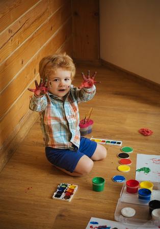 芸術品や工芸品。子供の学習とプレーします。子色手、ガッシュの塗料および図面を示します。想像力、創造性と自由の概念。木製の床の上に座っ