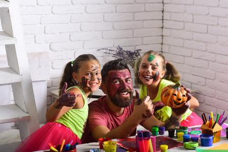 Halloween-familie met kleurrijke verf. Halloween-kinderen met gelukkig gezicht in verf. Feestdagen en feestviering. Kinderen of kleine meisjes met een bebaarde man vader houden pompoen. Kunst en kleuren schilderen. Stockfoto
