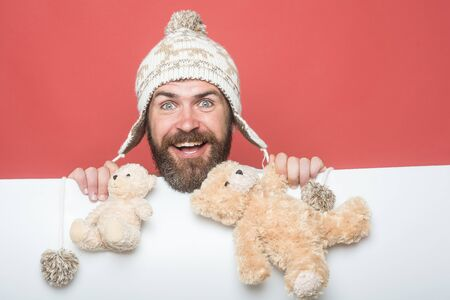 Guy with happy face in winter hat. Holiday celebration and party. Christmas and birthday. Hipster with toy on red white background. Man with long beard hold bear toy.