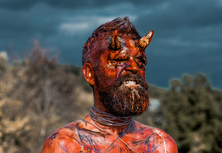 Halloween dragon creature on natural environment. Temptation, hell, evil, horror, darkness concept. Satan with red blood and wounds on face skin. Demon man with beard. Devil head with bloody horns