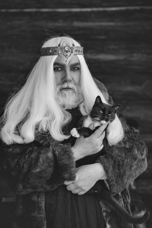 Druid old man with long grey hair and beard with crown in fur coat holds cat on dark background Stock Photo