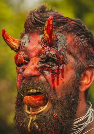 Halloween devil head with bloody horns. Demon man with beard showing tongue. Satan with red blood and wounds on face skin. Dragon, creature, witcher. Temptation, hell, evil, horror, darkness concept.