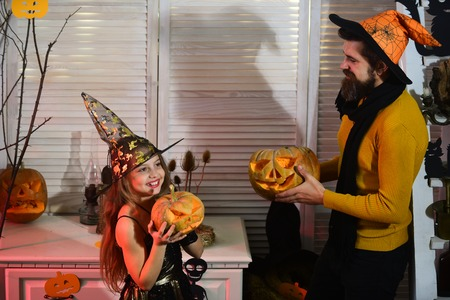 Father and daughter with Halloween decor. Wizard and little witch in hats hold jack o lanterns. Halloween party concept. Girl and bearded man with happy faces on red spooky carnival room background
