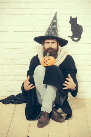 Halloween man in witch hat sitting on floor. Hipster with pumpkin and black cat symbol on wall. Evil spell and magic. Bad luck concept. Autumn holidays celebration. Stock Photo