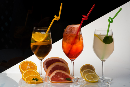 Alcoholic beverage and fruit at restaurant. Drink and food. Cocktails on black background. Party and summer vacation. Fruit slice and cocktail glass at bar. Stock Photo
