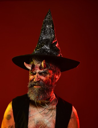 Halloween devil hipster with beard, blood, wounds on face. Man with satan horns in witch hat on red background. Hell, death, evil, horror concept. Might, magic, witchcraft
