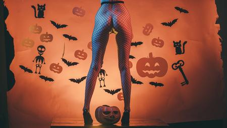 Halloween-billen van vrouw bij pompoen. Benen van meisje op skelet en knuppelverschrikkingsachtergrond. feest en feest. Halloween vakantie en feest. sexy vrouwelijke benen in visnetlegging en schoenen.