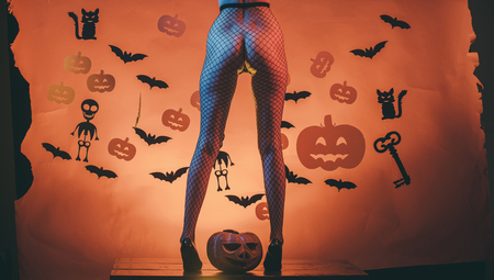 Halloween buttocks of woman at pumpkin. Legs of girl on skeleton and bat horror background. party and celebration. Halloween Holiday and celebration. sexy female legs in fishnet tights and shoes. Stok Fotoğraf