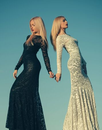 Choice, decision and future. Two girls with long blond hair posing on blue sky. Opposites and contrasts concept. Fashion and beauty. Women wearing black and white dresses.