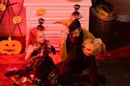 Wizard and little witch in hats hold pumpkin. Girl and bearded man with smiling faces on red spooky carnival room background. Halloween party concept. Father and daughter with Halloween decor