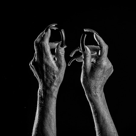 Closeup view of two female old scary mystic hands with long black nails on fingers of witch zomby demon or devil on halloween holiday character in studio indoor on dark background, square picture Stock Photo