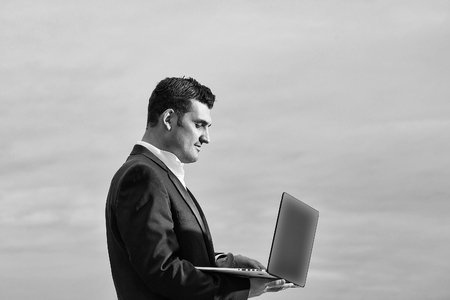 handsome male businessman with serious face in black formal jacket and white shirt working on laptop outdoor on cloudy sky background Reklamní fotografie