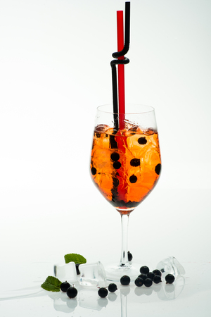 Alcoholic beverage and currant berry at restaurant. Party and summer vacation. Cocktail with blueberry isolated on white background. Drink and food. Drinking straw in cocktail glass at bar.