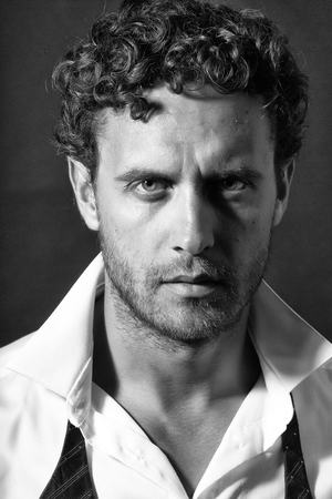 Handsome sexy man with curly hair and unshaven face in white shirt and red untied bow on black background