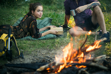 Woman read book and man with mug at campfire. Couple of hikers relax at bonfire on nature. Summer vacation concept. Camping, hiking, lifestyle. Фото со стока