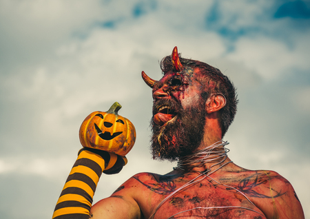 Halloween evil, horror, hell concept. Satan with red tongue, beard, blood, wounds on face. Devil man holding pumpkin in striped sock. Dragon with jack o lantern. Demon with bloody horns on head.