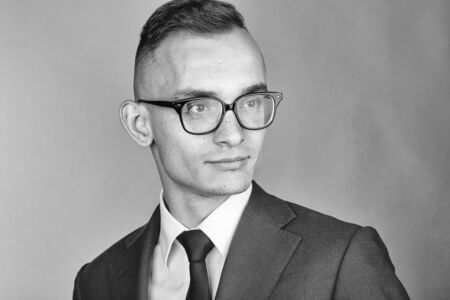 young fashion businessman with nerd glasses and stylish hairdo in jacket with tie on studio background