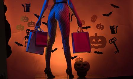 De sexy benen van Halloween in visnetlegging en schoenen. billen van vrouw bij pompoen houden boodschappentas. Benen van meisje op skelet en knuppelachtergrond. Halloween vakantie feest. winkel- en feestpakket.