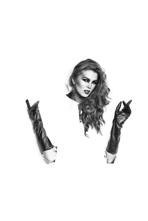 Pretty woman with long lush curly hair with hands in black leather gloves in torn paper isolated on white background