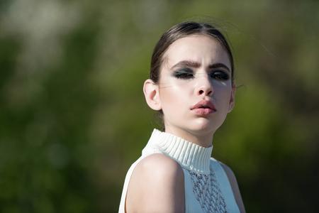 Vrouw of meisje dragen gouden oorbellen met make-up op gezicht op wazig natuurlijke omgeving. Mode, schoonheid, visage concept, kopie ruimte Stockfoto
