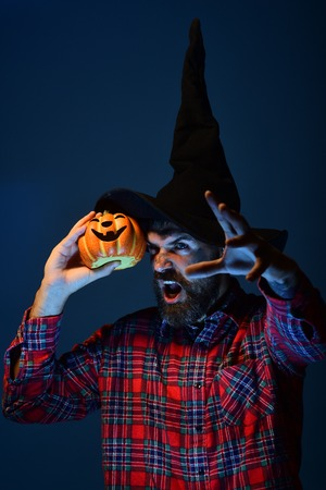Halloween trick or treat. Man in witch hat holding pumpkin on blue background. Autumn holiday celebration. Wizard hipster with scary face and jack o lantern. Mystery and magic concept. Stock Photo