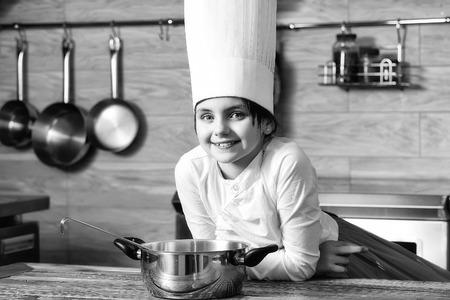 냄비와 함께 요리 모자에있는 여자 아기