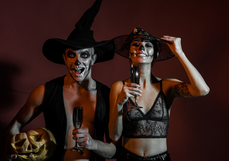 Halloween couple with makeup on brown background. Couple in love with pumpkin and wine glass. woman and man has happy face in witch hat. Halloween Holiday and celebration. Zombie party and horror.
