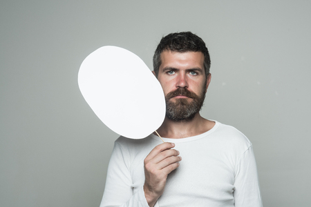 Barber fashion and beauty. Feeling and emotions. Man with long beard and mustache. Hipster with serious face hold paper nameplate. Guy or bearded man on grey background., copy space