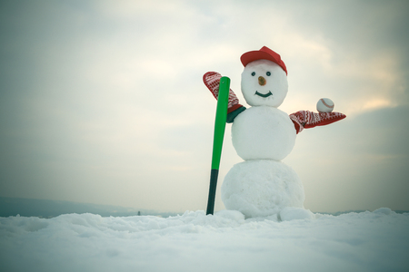 christmas snowman in cap with baseball bat in winter, sport