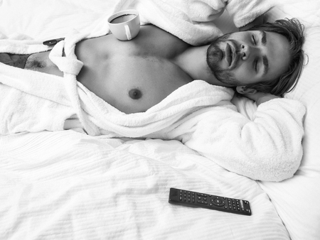 young handsome bearded man in white terry bathrobe sleeping on bed in hotel bedroom with remote control and coffee cup, has bare chest