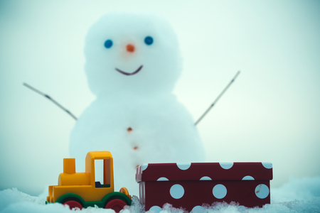 Toy train and present box on snow. Blur snowman with smiley face on white background. Christmas and new year. Winter holidays celebration concept