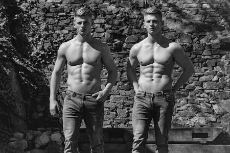 双子兄弟 2 筋肉ボディビルダーの裸の壁画の背景にポケットにジーンズ スタンド手で胸の強い若い男性セクシーなモデル