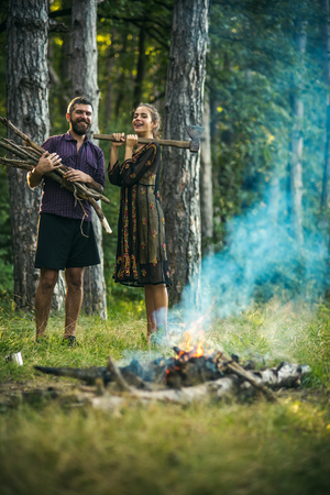 Man with bunch of firewood. Woman lumberjack hold axe. Couple of hikers make bonfire in forest. Camping, hiking, lifestyle. Summer vacation concept.