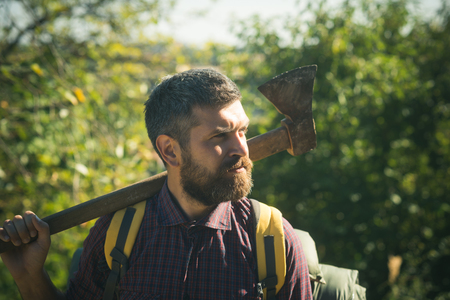 Man lumberjack with beard hold axe on shoulder on sunny day on natural landscape. Logging and chopping concept.