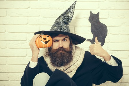 Halloween evil spell and magic. Man in witch hat with pumpkin sitting on floor. Autumn holidays celebration. Bad luck concept. Hipster showing thumbs up with black cat symbol on wall.