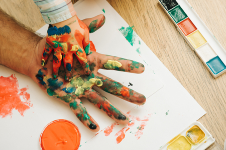 Care, love or adoption concept. Fathers day and family. Arts and handprint painting. Hands in colorful paints and multicolor palette on white paper. Support and protection. Stock Photo