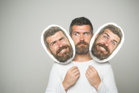 Hipster with serious, happy and scary face hold portrait nameplate. Barber fashion and beauty. Feeling and emotions. Man with long beard and mustache. Guy or bearded man on grey background.