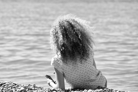 Young woman back view with blond curly hair wearing rosy blouse playing with smart phone sitting on pebble beach on blue sea shore sunny summer day on blurred seascape background, horizontal picture