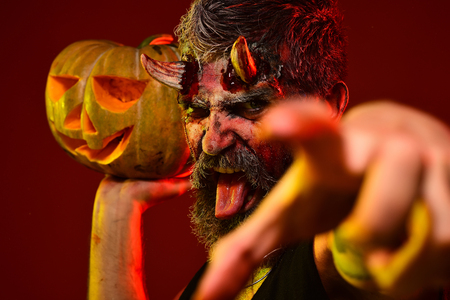Halloween trick or treat. Satan show tongue with bloody horns, beard, blood, wounds. Darkness and light concept. Man devil hold pumpkin on red background. Demon point finger with jack o lantern. Stock Photo