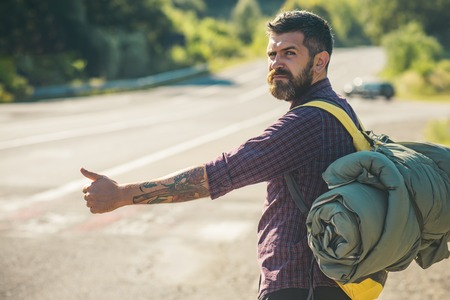 Man with backpack hitchhiking on road. Hipster hiker show thumbs up hand gesture on sunny day. Tourist traveler travel auto stop. Summer vacation concept. Adventure, discovery, wanderlust.