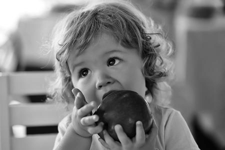 귀여운 국방과 금발 머리 개미 아이드 작은 아이가 물어 뜯고 먹는 큰 빨간 사과 과일 초상화 배경 흐리게, 가로 그림 스톡 콘텐츠