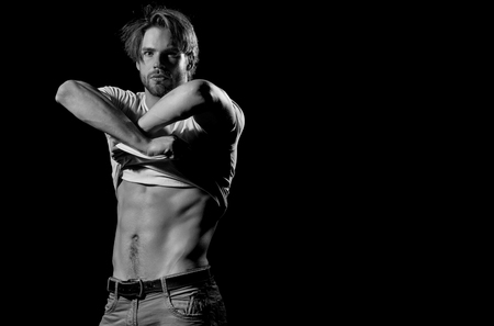 Handsome man or unshaven macho, bodybuilder, with stylish blond hair, haircut, undressing white tshirt, showing sexy, muscular torso, six packs, abs, male striptease on black background, copy space
